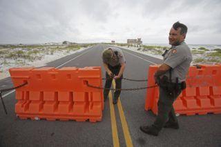Pensacola, 2018. május 29. Az amerikai nemzeti parki szolgálat két tagja lezárja a 399 autópályát az Alberto névre keresztelt szubtrópusi vihar megérkezése elõtt a floridai Pensacolában 2018. május 28-án. Az idei hurrikánszezon elsõ vihara miatt több amerikai szövetségi államban szükséghelyzetet hirdettek. (MTI/AP/Dan Anderson)