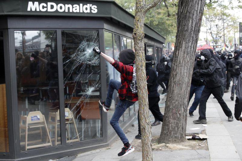 Párizs, 2018. május 1. Tüntetõk rugdossák egy McDonald's étterem üvegeit Párizsban 2018. május 1-jén. (MTI/EPA/Yoan Valat)