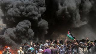 Gáza, 2018. május 14. Palesztin tüntetõk égõ gumiabroncsok füstjében az enklávét Izraeltõl elválasztó kerítés mellett, Gáza városától keletre 2018. május 14-én. A nap folyamán több tízezer palesztin tiltakozott az amerikai nagykövetség Tel-Avivbõl Jeruzsálembe való átköltöztetése miatt. A palesztin egészségügyi hatóság összesítése szerint a Gázai övezet határán zajló összecsapásokban 52 palesztin vesztette életét, s több mint kétezren megsérültek. Az izraeli katonák könnygázzal és éles lõszerrel válaszoltak a palesztinok kerítést megközelítésére tett kísérleteire.(MTI/EPA/Mohammed Szaber)