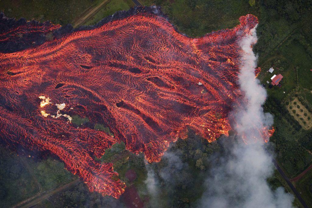 Pahoa, 2018. május 20. Izzó lávafolyam zúdul ki a Kilauea tûzhányó kráterébõl a hawaii Nagy-szigeten fekvõ Pahoa környékén 2018. május 19-én. A világ egyik legaktívabb tûzhányójának számító Kilauea vulkáni tevékenysége május 3-a óta tart. Azóta mintegy 2000 embert telepítettek ki otthonaikból, további ezrek önként távoztak, mert a tûzhányó repedéseibõl mérgezõ gázok áradnak a környékre. A Kilaueából feltörõ magma eddig 44 házat pusztított el. (MTI/EPA/Bruce Omori/Paradise Helicopters)