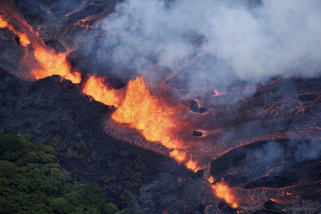 Pahoa, 2018. május 20. Izzó láva ömlik a Kilauea tûzhányó kráterébõl a hawaii Nagy-szigeten fekvõ Pahoa környékén 2018. május 19-én. A világ egyik legaktívabb tûzhányójának számító Kilauea vulkáni tevékenysége május 3-a óta tart. Azóta mintegy 2000 embert telepítettek ki otthonaikból, további ezrek önként távoztak, mert a tûzhányó repedéseibõl mérgezõ gázok áradnak a környékre. A Kilaueából feltörõ magma eddig 44 házat pusztított el. (MTI/EPA/Bruce Omori/Paradise Helicopters)