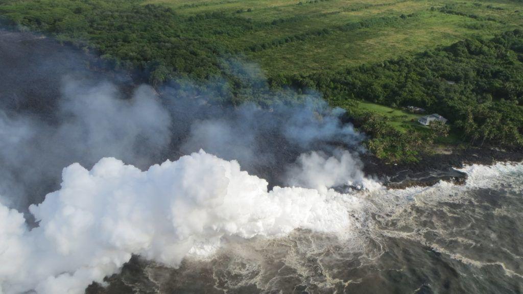 Pahoa, 2018. május 21. Az amerikai földtani intézet (USGS) által közreadott képen gõzfüggöny csap fel a vízpartról, amint a Kilauea tûzhányó lávafolyama beleömlik a Csendes-óceánba a hawaii Nagy-szigeten fekvõ Pahoa város környékén 2018. május 20-án. A világ egyik legaktívabb tûzhányójának számító Kilauea vulkáni tevékenysége május 3. óta tart. A környékén kötelezõ kitelepítés van érvényben, a lávafolyam eddig 44 házat pusztított el. Jelenleg tilos az óceánban való fürdõzés a térségben, mert a láva és a víz találkozásakor veszélyes sósav keletkezhet, a vulkán pedig egyre nagyobb mértékben lövell ki szintén mérgezõ kén-dioxidot. (MTI/EPA/USGS)