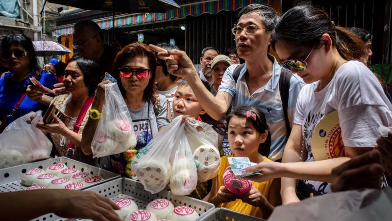"""Customers buy traditional buns made for the annual Cheung Chau bun festival in Hong Kong on May 3, 2017. Tens of thousands gathered in Hong Kong on May 3 for one of its most colourful festivals, a whirlwind of music and costume culminating in a dramatic climb up a precipitous """"bun tower"""". / AFP PHOTO / Anthony WALLACE"""