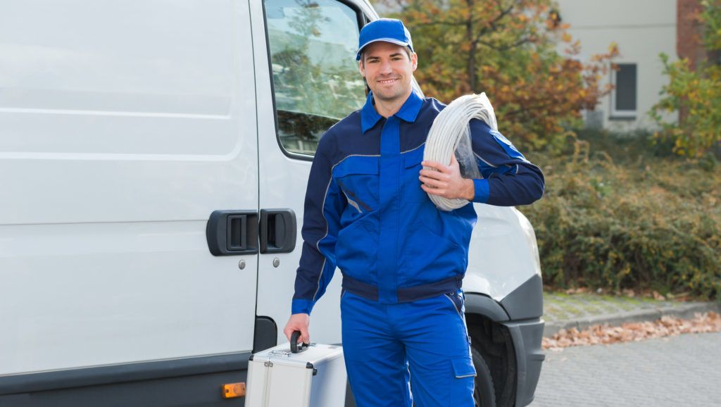 Portrait of confident electrician with cable coil and toolbox standing outside truck