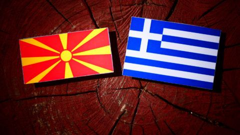 Macedonian flag with Greek flag on a tree stump isolated