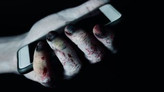 closeup of a scary and bloody hand holding a smartphone against a black background