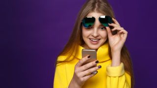 Girl in a yellow sweater reads the message on phone, a happy smile. Isolate on a violet background