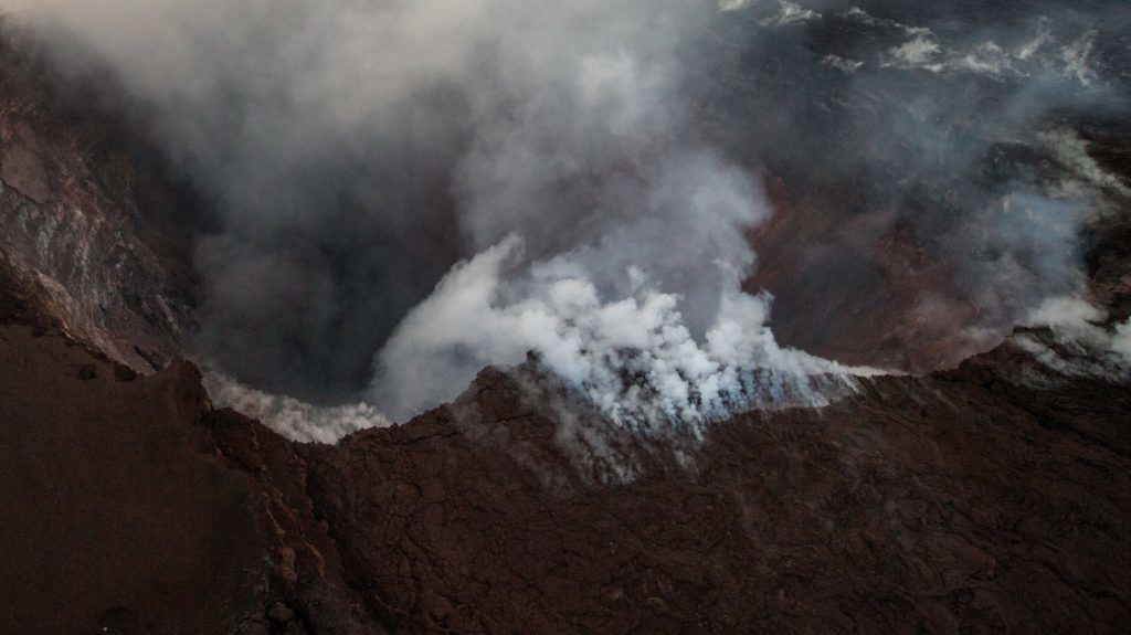 Pahoa, 2018. május 4. Füst és hamu száll fel a Kilauea tûzhányó kráterébõl a Hawaii-szigeti Pahoa város közelében 2018. május 2-án, miután 5-ös erõsségû földrengés rázta meg a csendes-óceáni szigetet. A földmozgás nyomán részlegesen beomlott a kürtõ és új repedések keletkeztek a vulkán oldalában, amelyekbõl forró pára és láva került a felszínre. A hatóságok figyelmeztetést adtak ki a térség lakott Leilani körzetében. (MTI/EPA/Bruce Omori)