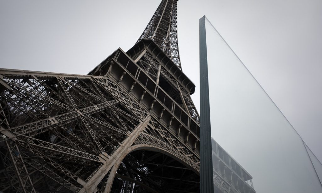 This picture taken on June 14, 2018 in Paris shows part of a bulletproof glass wall to be set around the Eiffel tower as an anti-terrorism measure. / AFP PHOTO / Philippe LOPEZ