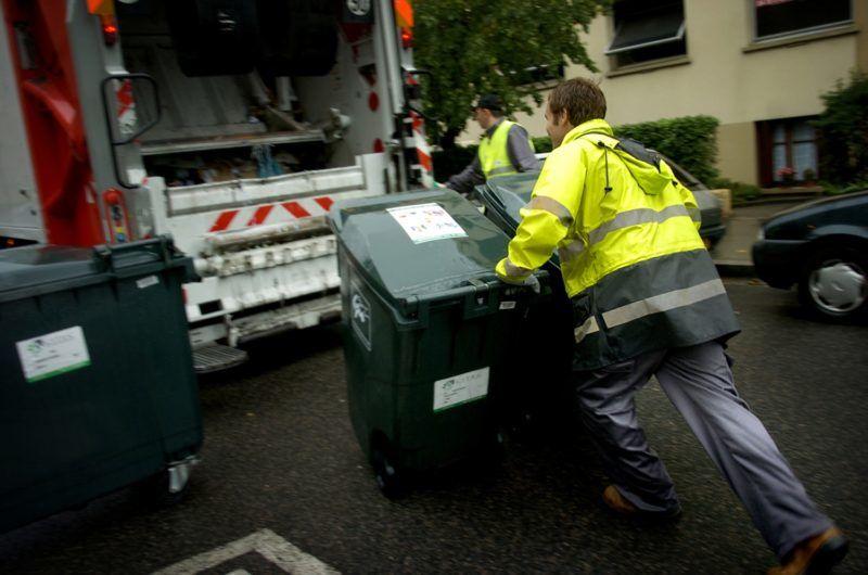 Dustmen push dumpsters to a waste truck, 06 July in Lyon, south France.  Des éboueurs poussent des bennes, le 06 juillet 2006 à Lyon, vers le camion de collecte des ordures destinées à être incinérées.  AFP PHOTO JEFF PACHOUD / AFP PHOTO / JEFF PACHOUD