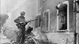 Un soldat américain tient en joue un soldat allemand lors de la bataille pour la libération de la France, dans l'ouest de la France en 1944. An American soldier points his rifle at a German soldier surrendering during the battle for France's liberation, western France, in 1944. / AFP PHOTO / STF