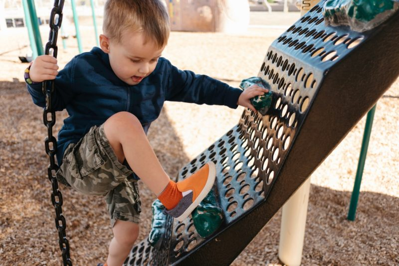 Boy climbing on playground climbing frame