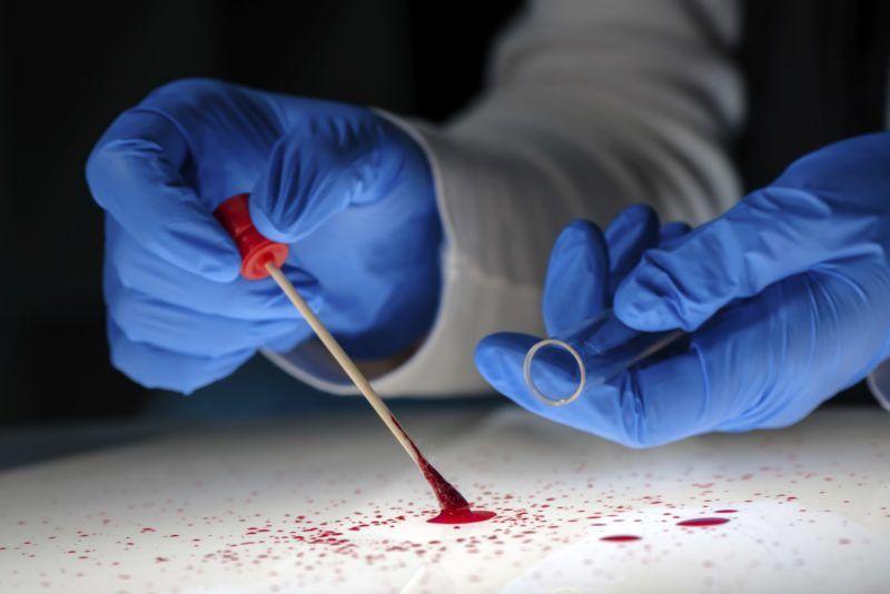 Forensic technician taking bloodstain sample.