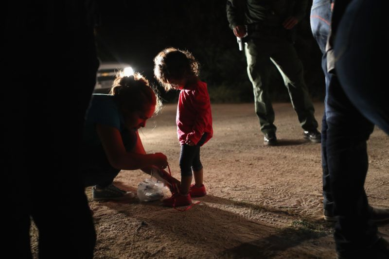 """MCALLEN, TX - JUNE 12: A Honduran mother removes her two-year-old daughter's shoe laces, as required by U.S. Border Patrol agents, after being detained near the U.S.-Mexico border on June 12, 2018 in McAllen, Texas. The asylum seekers had rafted across the Rio Grande from Mexico and were detained by federal authorities before being sent to a processing center for possible separation. Customs and Border Protection (CBP) is executing the Trump administration's """"zero tolerance"""" policy towards undocumented immigrants. U.S. Attorney General Jeff Sessions also said that domestic and gang violence in immigrants' country of origin would no longer qualify them for political asylum status.   John Moore/Getty Images/AFP"""