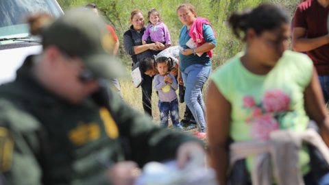 """MCALLEN, TX - JUNE 12: Central American asylum seekers wait as U.S. Border Patrol agents take them into custody on June 12, 2018 near McAllen, Texas. The families were then sent to a U.S. Customs and Border Protection (CBP) processing center for possible separation. U.S. border authorities are executing the Trump administration's """"zero tolerance"""" policy towards undocumented immigrants. U.S. Attorney General Jeff Sessions also said that domestic and gang violence in immigrants' country of origin would no longer qualify them for political asylum status.   John Moore/Getty Images/AFP"""