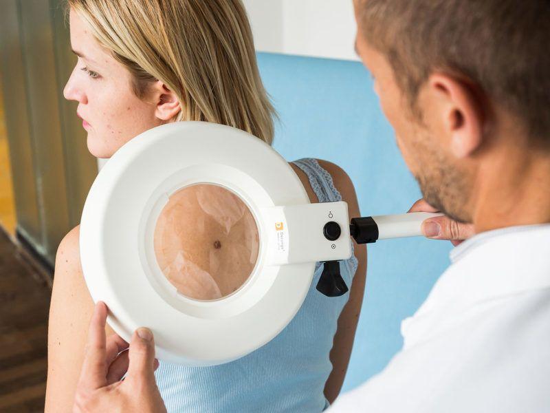 Doctor examining the skin of a woman. Paris, France VOISIN/PHANIE