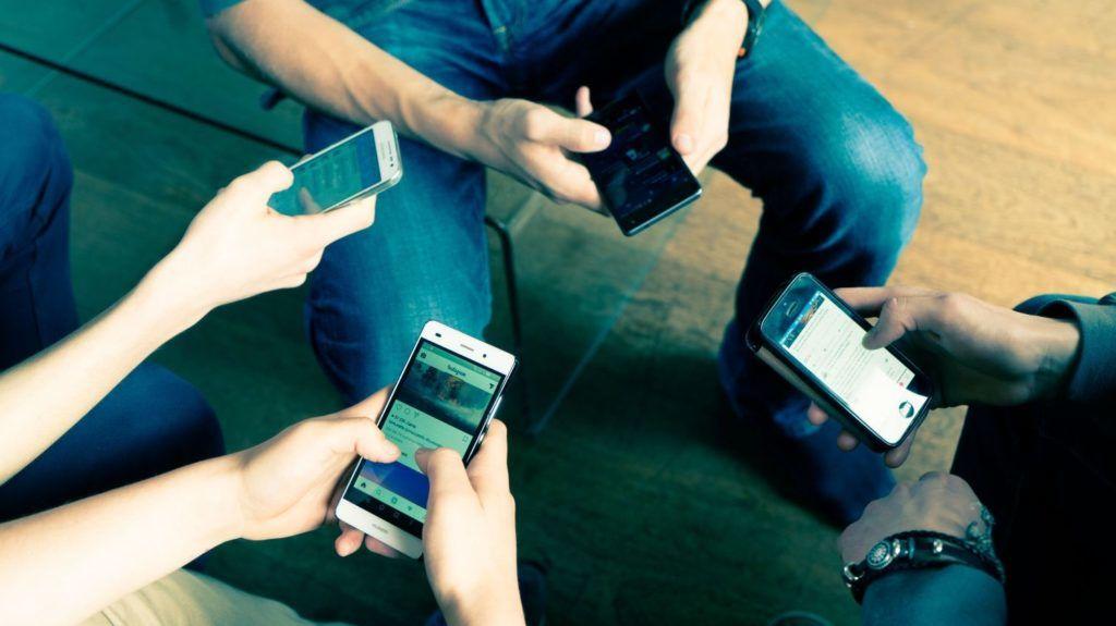 Group of teenagers using smartphones.     VOISIN/PHANIE