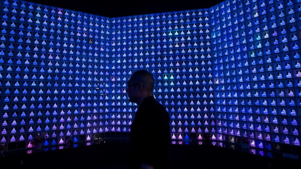 Koukokuji temple chief priest Yajima Taijun walks through the Ruriden columbarium as glass Buddha alters are lit up on July 7, 2016 in Tokyo, Japan. Operated by the Koukokuji buddhist temple, The Ruriden columbarium at the Koukoko-ji Temple houses over 2,046 crystal Buddha statues, each illuminated by high-powered LED lights. Behind each Buddha is a drawer storing people's ashes. An IC card allows the owner of the alter to access the building and lights up the corresponding statue. The ashes are stored for 33 years before being buried below the Ruriden, currently 900 alters are in use as of July 2016.  (Photo by Richard Atrero de Guzman/NurPhoto)