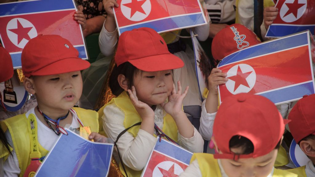 Children wave North Korea national flags as they take part in a joint friendship gathering to mark the 68th anniversary of an 'International Children's Day' event at the Kaeson Youth Park in Pyongyang on June 1, 2018. / AFP PHOTO / KIM Won-Jin