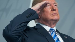 """(FILES) In this file photo taken on June 01, 2018 US President Donald Trump salutes during a Change of Command ceremony as Admiral Karl Schultz takes over from Admiral Paul Zukunft as the Commandant of the US Coast Guard at US Coast Guard Headquarters in Washington, DC, June 1, 2018. US President Donald Trump on Monday asserted an """"absolute right"""" to pardon himself, once again lashing out at a probe into possible collusion with Russian election meddling and obstruction of justice. / AFP PHOTO / SAUL LOEB"""