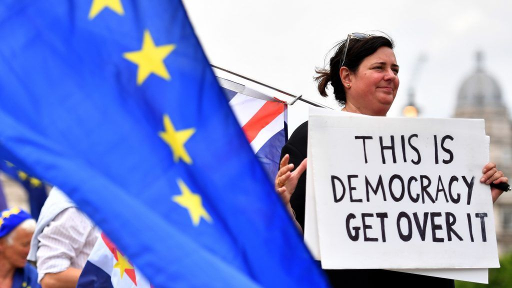 A pro-EU demonstrator holds a placard  during an anti-Brexit protest outside the Houses of Parliament in London on June 13, 2018.  / AFP PHOTO / Ben STANSALL
