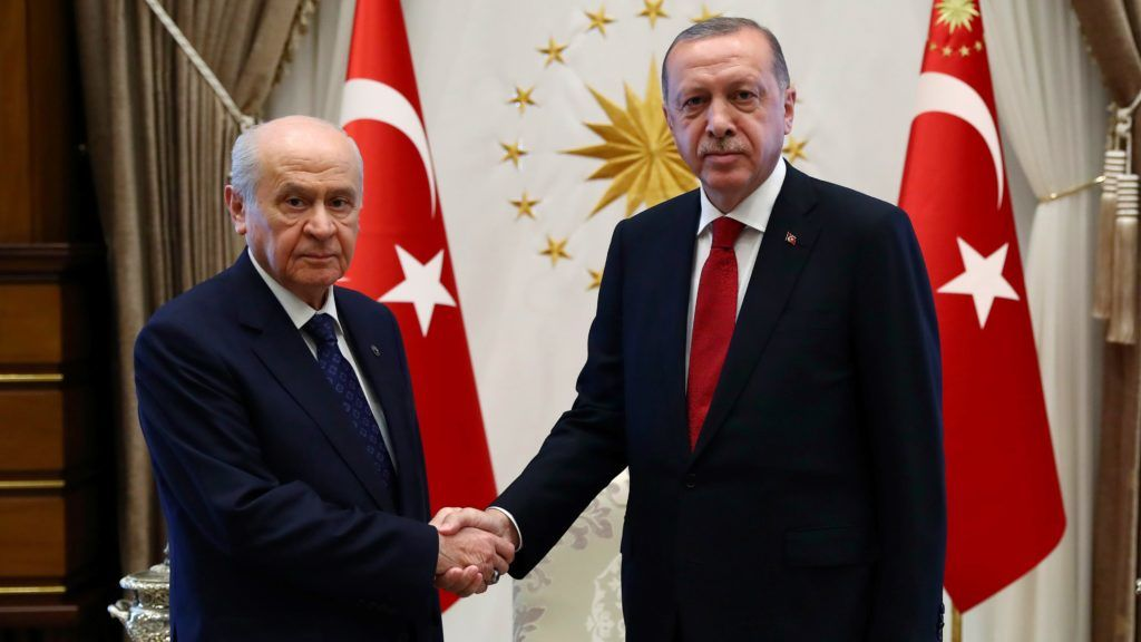 """This handout photo released by the Turkish Presidential Press Service shows Devlet Bahceli (L) leader of the Nationalist Movement Party (MHP) shaking hand with Turkey's President Recep Tayyip Erdogan (R) before a meeting at the presidential palace in Ankara, on June 27, 2018.  / AFP PHOTO / KAYHAN OZER / RESTRICTED TO EDITORIAL USE - MANDATORY CREDIT """"AFP PHOTO /TURKISH PRESIDENTIAL PRESS SERVICE' KAYHAN OZER"""" - NO MARKETING NO ADVERTISING CAMPAIGNS - DISTRIBUTED AS A SERVICE TO CLIENTS"""