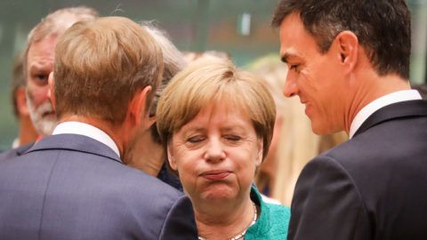 Germany's Chancellor Angela Merkel (C) reacts as she speaks with European Council President Donald Tusk (L) and Spain's Prime Minister Pedro Sanchez during an European Union leaders' summit focused on migration, Brexit and eurozone reforms on June 28, 2018 at the Europa building in Brussels. The two-day meeting in Brussels is expected to be dominated by deep divisions over migration, with German Chancellor saying the issue could decide the fate of the bloc itself. / AFP PHOTO / Ludovic MARIN