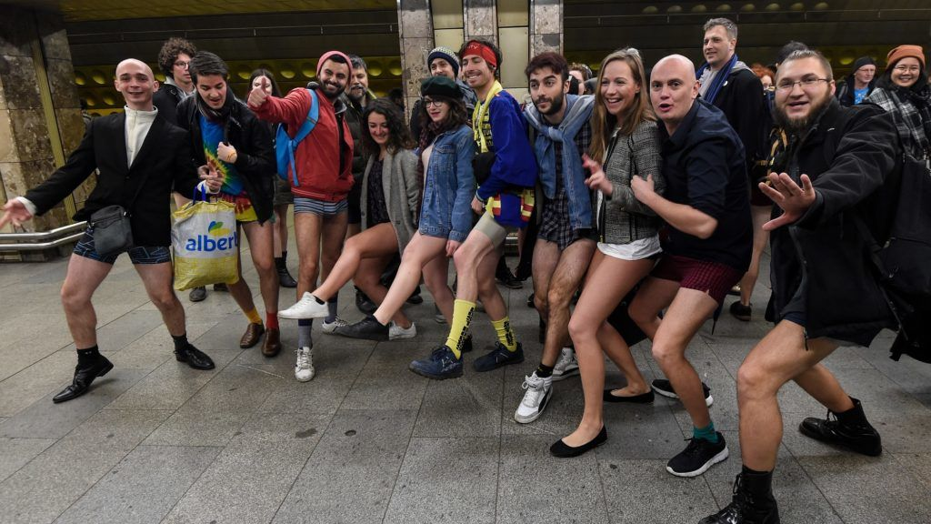 """Passengers without pants pose for photographers prior to attend the """"No Pants Subway Ride"""" on January 7, 2018 in Prague. The No Pants Subway Ride is an annual event which was started in 2002 by Improv Everywhere in New York, the goal is for riders to get on the subway train dressed in normal winter clothes without pants and stay serious. / AFP PHOTO / Michal CIZEK"""