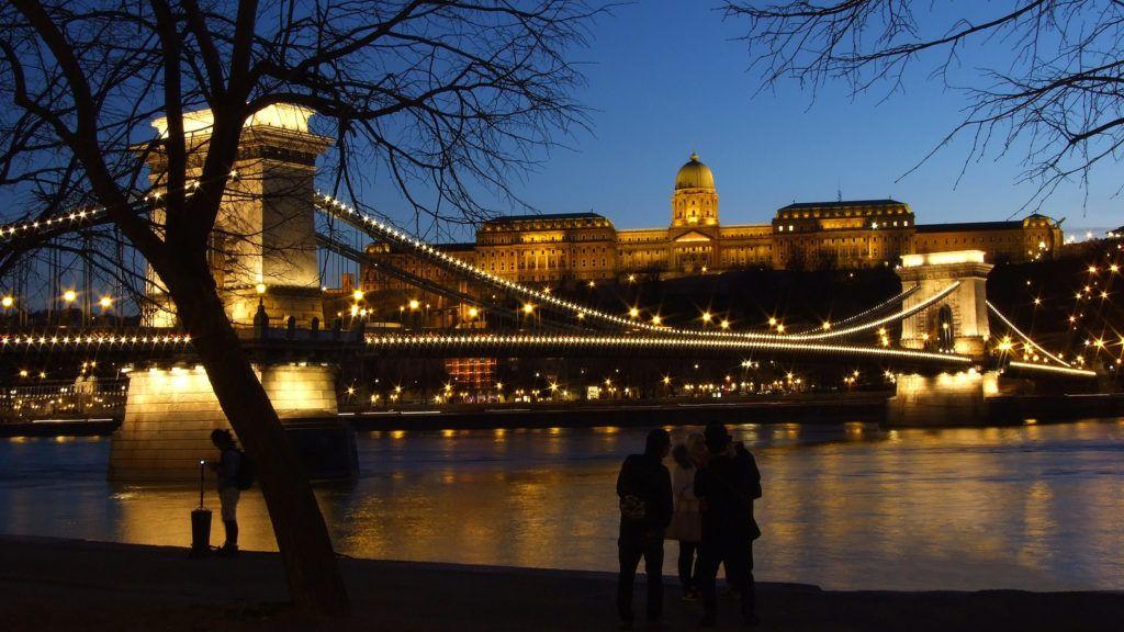 Budapest, 2018. március 13. Külföldi turisták fényképezik a kivilágított budai Várat és a Duna fölött átívelõ Széchenyi Lánchídat alkonyi fényben a folyópartról. MTVA/Bizományosi: Jászai Csaba  *************************** Kedves Felhasználó! Ez a fotó nem a Duna Médiaszolgáltató Zrt./MTI által készített és kiadott fényképfelvétel, így harmadik személy által támasztott bárminemû – különösen szerzõi jogi, szomszédos jogi és személyiségi jogi – igényért a fotó készítõje közvetlenül maga áll helyt, az MTVA felelõssége e körben kizárt.