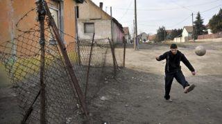 """Monor, 2010. április 23.Egy fiú focizik a Bercsényi utcában.  A monori Tabán, nagyrészt roma származásúak által lakott szegénytelepén az itt élő 400 lakó kétharmada gyermek. A Máltai szeretetszolgálat 4 éve elkezdett integrációs programja keretében, egy általuk felállított """"hangárban"""" a kisebbeknek játszóházat, az iskoláskorúaknak tanulószobát működtetnek, ahol 5-6 gépből álló számítógépes hálózat teszi hozzáférhetővé a világhálót. Korábban felnőtt oktatás is működött azok számára, akik nem fejezték be a 8 osztályt, szeptembertől újra indítják ezt a programot. A szeretet szolgálat munkatársai úgy gondolják, hogy a romák oktatása, felzárkóztatása teheti lehetővé az integrációt a többségi társadalomba.MTI Fotó: Beliczay László"""