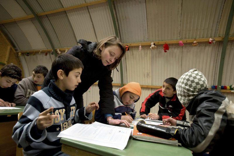 """Monor, 2010. április 23.Nagy Zsuzsanna tanítónő, szociális munkás foglalkozik a gyerekekkel a Máltai Szeretetszolgálat segítségével épített közösségi épületben, a """"hangárban"""" működő játszóházban.  A monori Tabán, nagyrészt roma származásúak által lakott szegénytelepén az itt élő 400 lakó kétharmada gyermek. A Máltai szeretetszolgálat 4 éve elkezdett integrációs programja keretében, egy általuk felállított """"hangárban"""" a kisebbeknek játszóházat, az iskoláskorúaknak tanulószobát működtetnek, ahol 5-6 gépből álló számítógépes hálózat teszi hozzáférhetővé a világhálót. Korábban felnőtt oktatás is működött azok számára, akik nem fejezték be a 8 osztályt, szeptembertől újra indítják ezt a programot. A szeretet szolgálat munkatársai úgy gondolják, hogy a romák oktatása, felzárkóztatása teheti lehetővé az integrációt a többségi társadalomba.MTI Fotó: Beliczay László"""