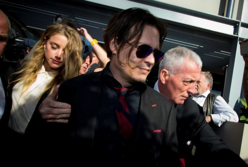 """US moviestar Johnny Depp (C) and his wife Amber Heard (L) leave the Gold Coast Courthouse in the Gold Coast on April 18, 2016.   Depp's wife Amber Heard pleaded guilty on April 18 to falsifying immigration documents in a case dubbed the """"war on terrier"""" after she brought her two pet dogs on their private jet into Australia last year. / AFP PHOTO / Patrick HAMILTON"""
