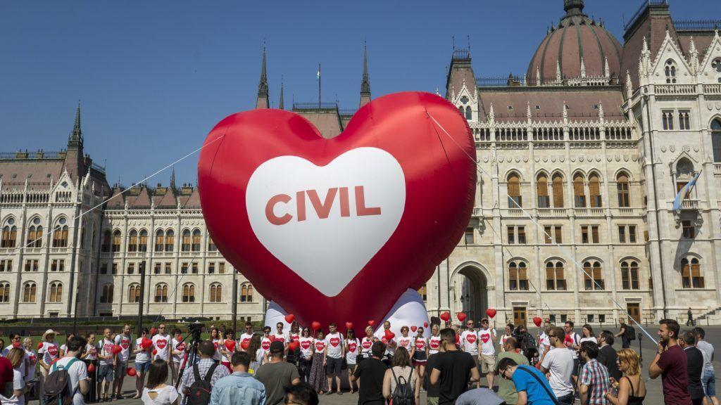 """Budapest, 2018. június 4. Résztvevõk egy szív alakú piros léggömb elõtt az Amnesty International (AI) """"Stop Soros"""" törvénycsomag ellen tartott szolidaritási akcióján a Parlament elõtti Kossuth téren 2018. június 4-én. A képviselõk június 5-én folytatják le az egyes törvényeknek a jogellenes bevándorlás elleni intézkedésekkel kapcsolatos módosításáról szóló törvényjavaslat, azaz a """"Stop Soros"""" vitáját. MTI Fotó: Mohai Balázs"""