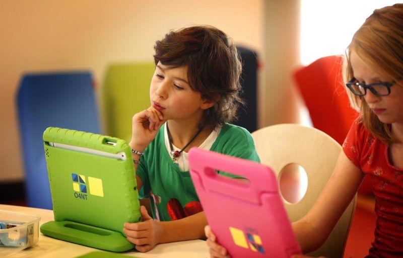 Sneek, 2013. augusztus 23. Gyerekek játszanak a saját táblagépükkel az észak-hollandiai Sneekben 2013. augusztus 21-én, az elsõ tanítási napon. Az O4NT alapítvány segítségével létrehozott iskolákban minden diák és minden tanár saját iPadet kap. Az alapítvány célja felkészíteni a gyerekeket az egyre jobban digitalizálódó világra. (MTI/EPA/Catrinus Van Der Veen)
