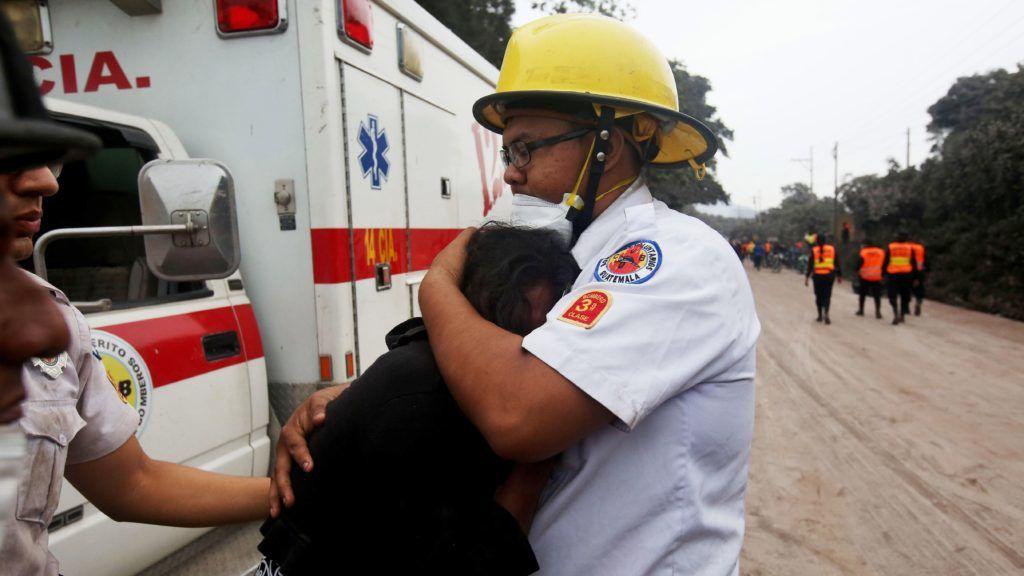 Escuintla, 2018. június 4. A Fuego tûzhányó elõzõ napi kitörésének áldozatául esett családtagjait siratja egy nõ egy tûzoltó karjában a dél-guatemalai Escuintlában 2018. június 4-én. A természeti katasztrófában legkevesebb huszonöten életüket vesztették, mintegy háromszázan égési sérüléseket szenvedtek, és többen eltûntek. (MTI/EPA/Esteban Biba)