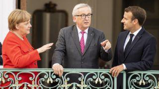 Meseberg, 2018. június 19.Angela Merkel német kancellár, Jean-Claude Juncker, az Európai Bizottság elnöke és Emmanuel Macron francia államfő (b-j) a német kormány vendégháza, a Berlin melletti mesebergi kastély erkélyén 2018. június 19-én, a német és a francia kormánynak a kastélyban tartott közös konzultációján. (MTI/EPA/Christian Bruna)