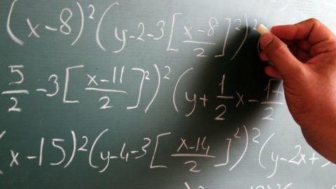 A Man writing a complex formulae on a blackboard