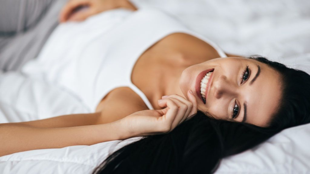 Attractive young woman looking at camera and smiling while lying on the bed at home