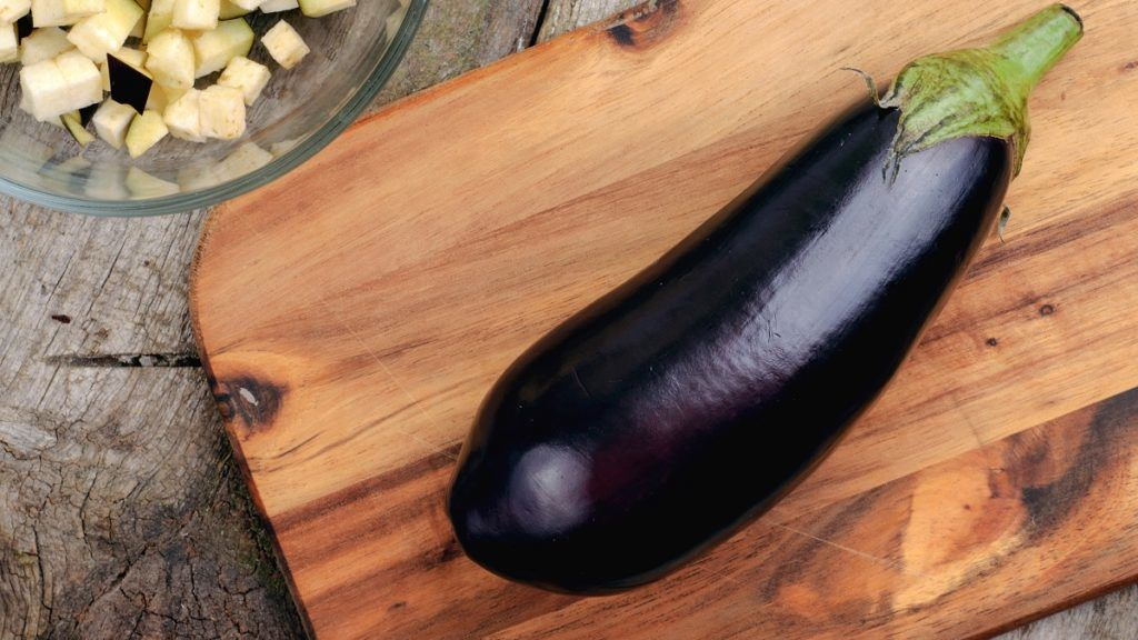 Purple eggplant on wooden table close up, top view