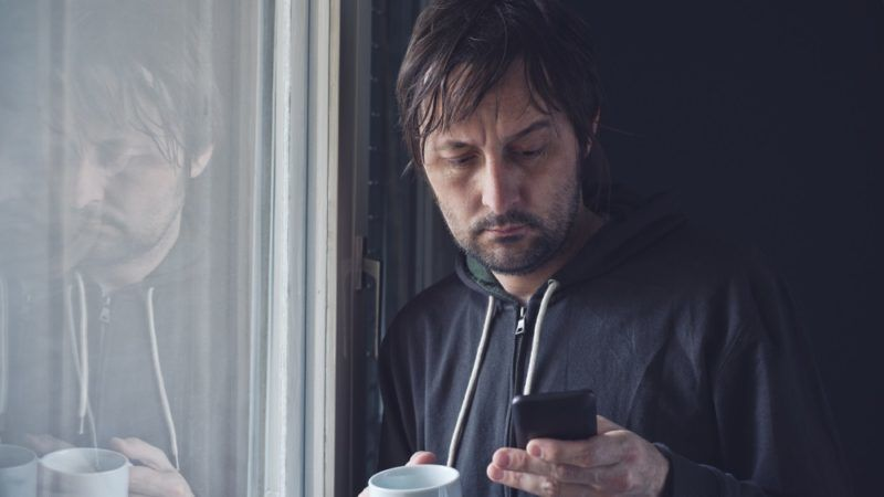 Adult Man Drinking Coffee And Reading Text Message or SMS on Mobile Phone in Morning by the Window. Selective Focus with Shallow Depth of Field.