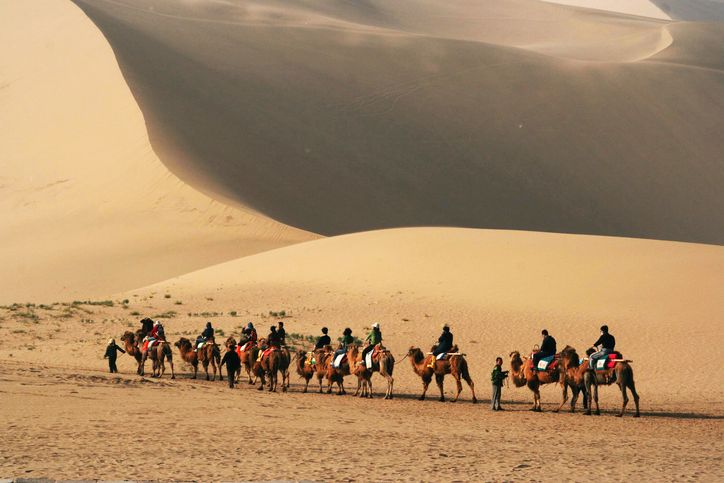 Tourists ride camels at Mingsha Shan (Singing Sand Dunes) in Dunhuang, China