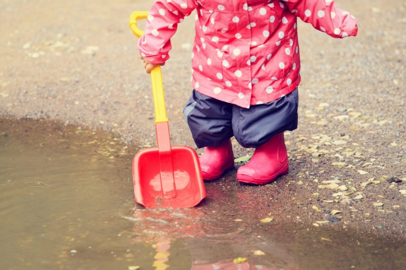 child playing in water puddle, kids outdoor activities