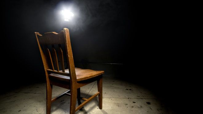 Isolated wooden chair in a dark scary prison with an interrogation spotlight.  The room looks like a dungeon or a prison cell where prisoners are interrogated.  The chair is empty and surrounded by dark shadows to give a feeling of terror and anxiety.  Some smoke is visible from the spotlight.