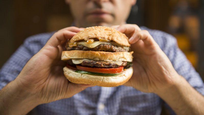 Caucasian man holding a big hamburger