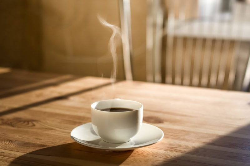 Kitchen interior in natural light, wood table with hot steaming drink on it