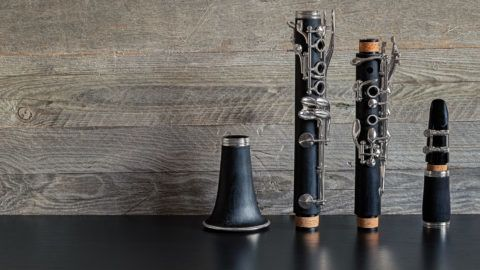 Black clarinet dismantled in four parts on a black table with a gray weathered wooden background