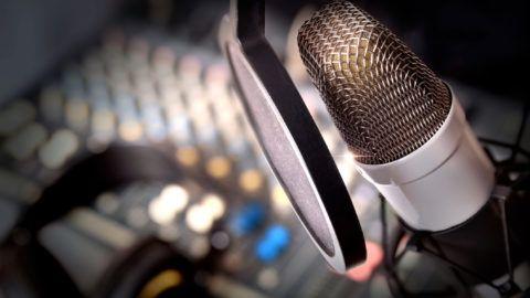 Recording equipment in studio. Studio microphone with headphones and mixer background. Elevated view