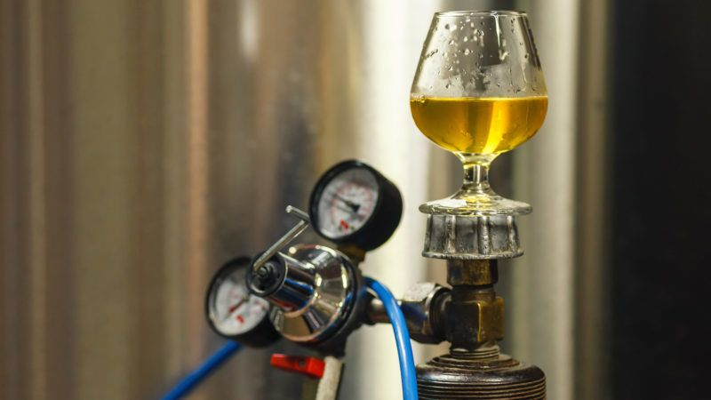 Tasting glass with clear lager beer standing on a gas tank at a brewery
