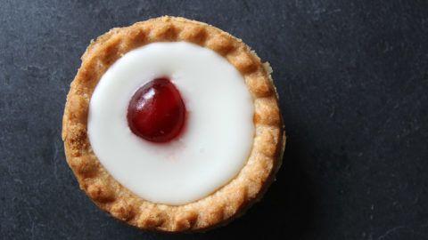 Cherry bakewell tart on dark background