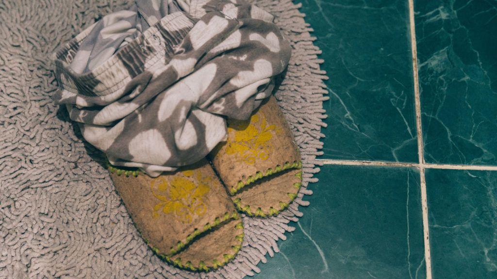 pants with slippers on bathroom tile floor